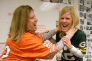 Two blonde women in NFL jerseys, in a playful rivalry of teams.